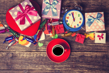Cup of coffee next to christmas toys on wooden table.