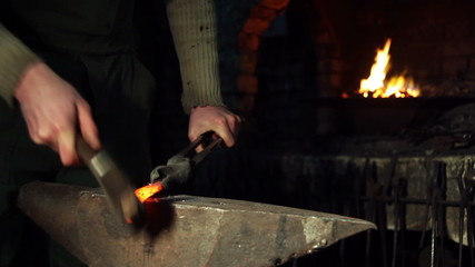 blacksmith who shapes hot steal with a hammer