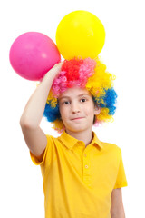 Smile boy in clown wig with two balloons