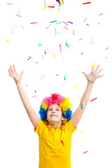 The young boy in clown wig throws colored confetti