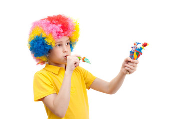 The boy in clown wig with wooden toys and whistle