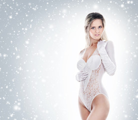Beautiful woman in bridal lingerie on a snowy background