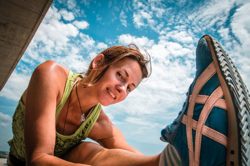 young happy woman does split fitness exercise blue sky backgroun