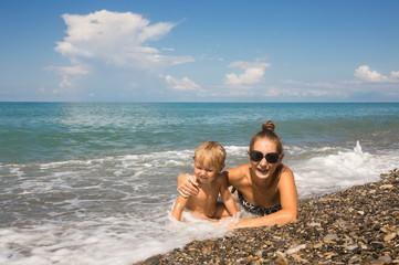 Mum with kid lie in sea waves