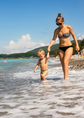 Mum with kid go near sea edge