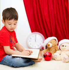 Cute boy reading a fairy tale. New Year