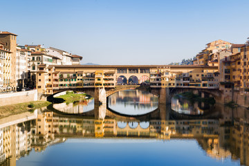 Antique bridge in Florence over Arno river with old houses