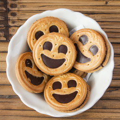 Round smiling chocolate cookies in a bowl over wooden background