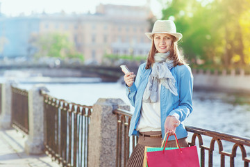 Beautiful girl with shopping bags and mobile phone