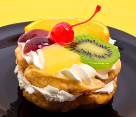 fruit cake with cream on black plate on yellow background