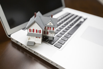 Miniature House on Laptop Computer