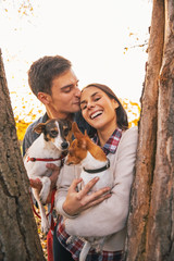 Portrait of romantic young couple with dogs outdoors