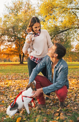 Happy young couple with dogs playing outdoors in autumn park