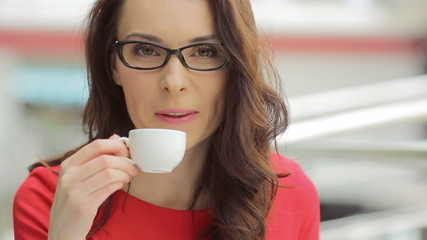 The young woman drinks coffee in the business center