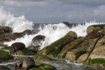 Closeup of waves crashing on rocks on shore