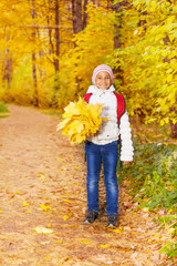 Cute African girl with bunch of maple leaves