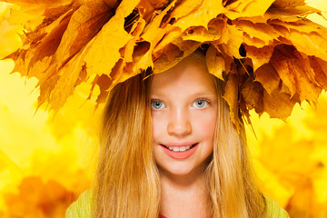 Beauty portrait of little girl in maple wreath