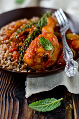 Chicken in tomato sauce with a garnish of buckwheat, rosemary, t