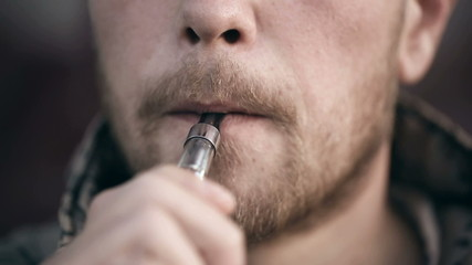 Bearded man smoking electronic cigarette.