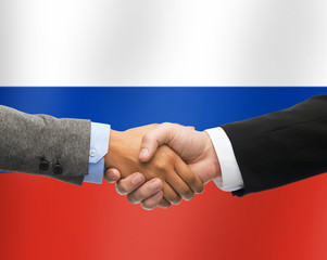 close up of handshake over russian flag