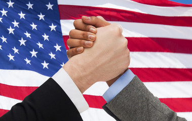 close up of hands arm wrestling over american flag