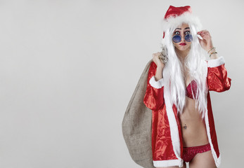 Female Santa Claus holding a jute sack and wearing sunglasses