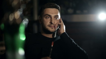 brutal man smokes a hookah in a cafe in the evening