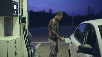 Filling station. A man fills his car with gasoline at night