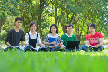 Happy group of students sitting at the park