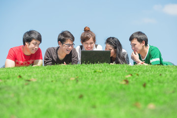 Group of students outdoors lying on grass and looking computer