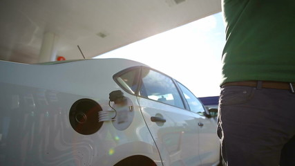 A man fills a white car quality biofuels at sunrise