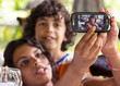 Hispanic teen and child taking a selfie with smartphone