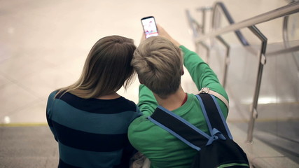 Loving couple take selfie sitting on the steps of the college