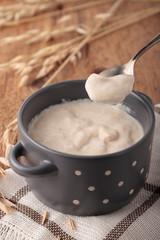 Porridge of oatmeal in gray ceramic pot