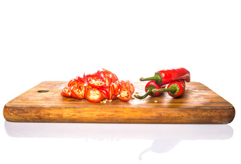 Slices of red chili peppers on wooden cutting board
