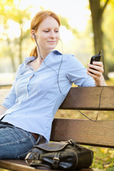 Woman Picking a Song on a Smartphone