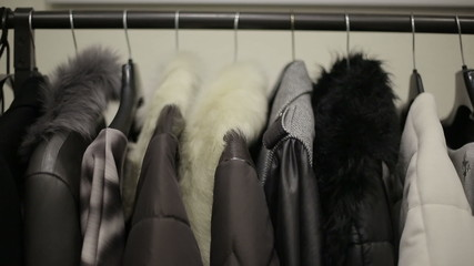 Design collection of winter clothing on hangers. Dolly shot
