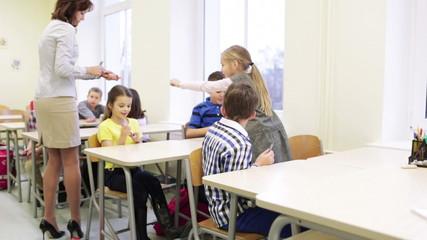 teacher giving pens to school kids in classroom