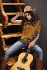 the girl with the guitar in a cowboy suit