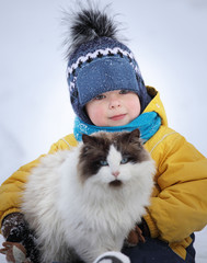 boy plays with a cat outdoors