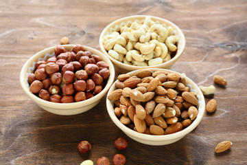nuts in bowls, cashews, almonds and hazelnuts