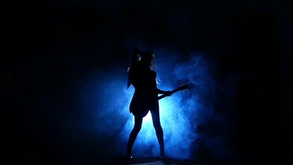 Silhouette of a young girl playing on electric guitar. Slow