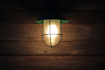 wall lantern attached to wooden wall .