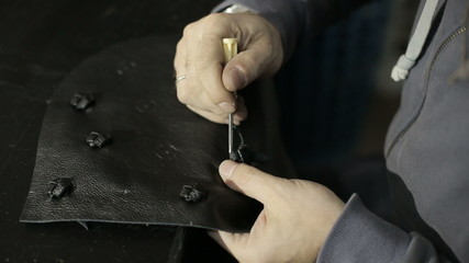 The man is engaged in manufacturing women's handbags.