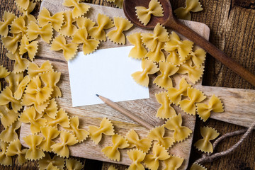 Lot of pasta with note on cutting board with kitchen spoon
