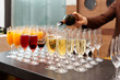 Bartender is pouring sparkling wine in glasses - 74173354