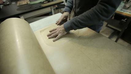 Cuts cardboard frame for making handbags.