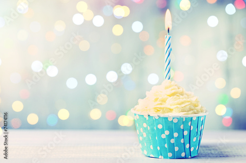 Delicious birthday cupcake on wooden table - 74174116