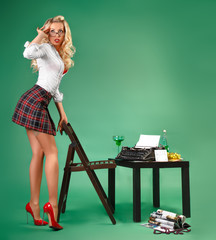 Sexy secretary in a short skirt typing on a typewriter