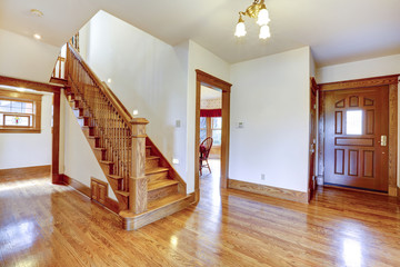Empty entrance hallway with wooden staircase
